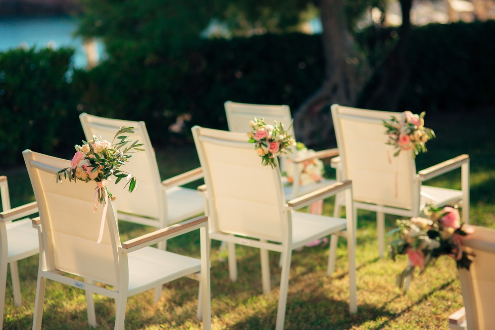 chairs decorated with flowers for a wedding ceremony